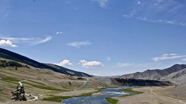 낮에는 햇빛과 푸른 하늘 아래 바위로 둘러싸인 강