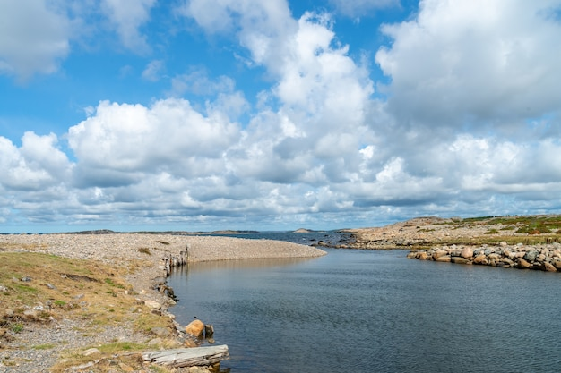 Река в окружении скал под солнечным светом и облачным небом днем