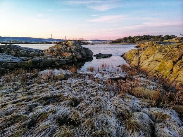 ノルウェー、オストルハルセンの日光の下で岩に囲まれた川