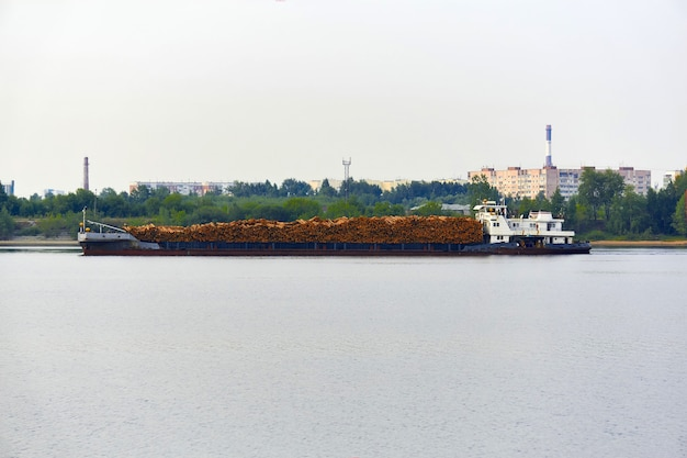 통나무를 실은 강 목재 운반선이 도시 해안을 지나