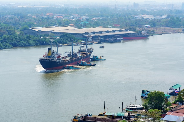 River tugboats pushing container ship in the middle of the chao phraya river