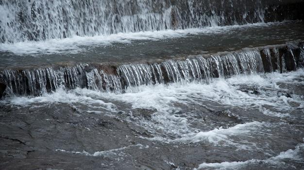 ダムの壁から流れ落ちる川の水