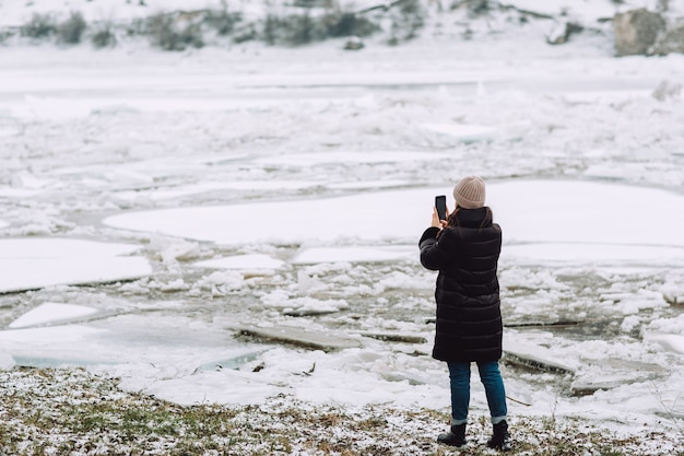 River in winter with a surface covered with a thick layer of cracked ice and ice floes. girl takes photo.