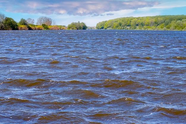 暗い水と風の間に波のある川