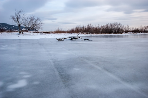 Река с замерзшей водой и старыми следами от машины