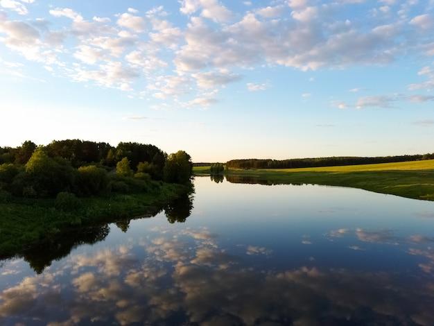 日没時の夏の日の雲の反射のある川。ドローンからの眺め。