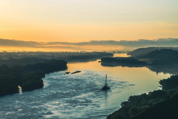 緑の海岸とコピースペースが付いている船の美しい川の風景。 river船は、川岸に沿ってクレーンでバージを牽引します。夜明けは穏やかなグレア水面で反射しました。