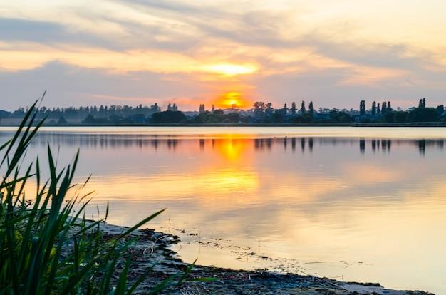 田舎の夏の日没の川岸