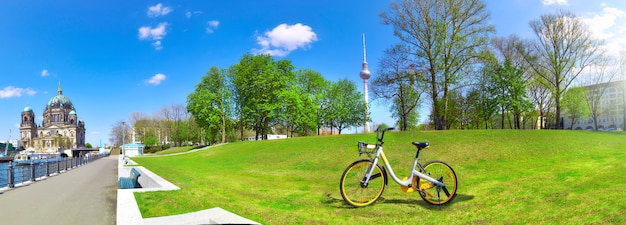 Riverside in central berlin with cathedral on the left, bike on the green lawn and television tower on alexanderplatz