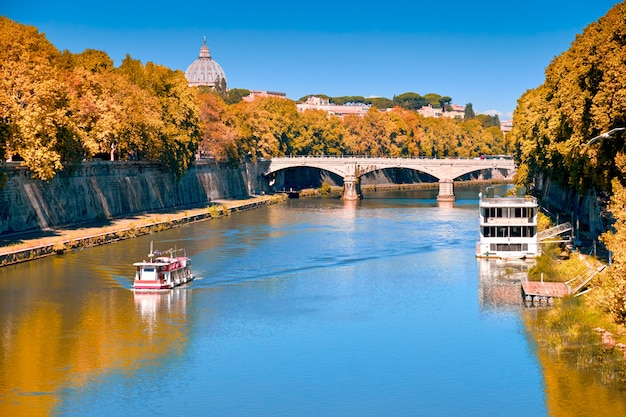 Riverside in fall with vatican st peter basilica and old bridge crossing tiber river in rome