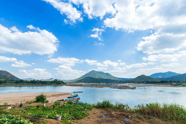 Riverside view of mae khong river and the a boat parked in port, mountain views of laos at the kaeng khud khu rapids at chiang khan i