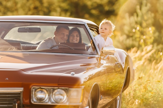 日没のレトロなスタイルのリビエラ。ユニークな車。かわいい金髪の少年が家族とレトロな車のホイールの後ろに座っています。両親は後部座席に座っており、少年は窓から覗きます。