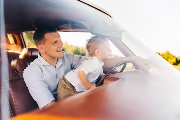 レトロなスタイルのリビエラ。ユニークな車。かわいい金髪の少年が父親と一緒にレトロな車のホイールの後ろに座っています。