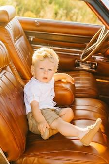 レトロなスタイルのリビエラ。ユニークな車。かわいい金髪の少年は革のインテリアとレトロな車のホイールの後ろに座っています。