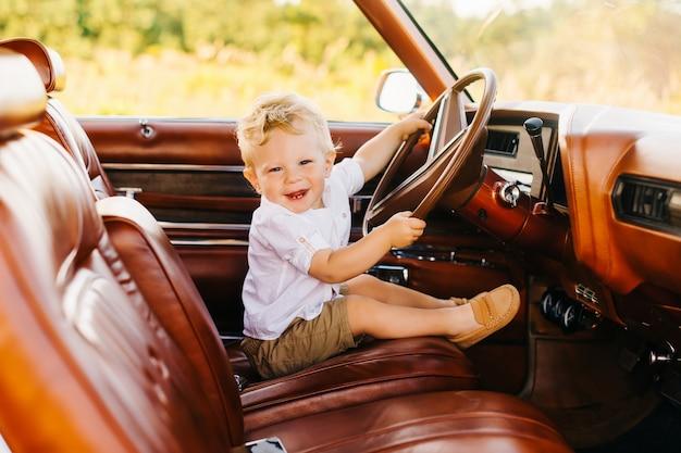 レトロなスタイルのリビエラ。ユニークな車。かわいい金髪の少年はレトロな車のホイールの後ろに座っています。