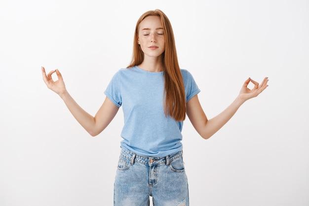 Rlieved redhead femmina con lentiggini sorridenti calmi chiudendo gli occhi e in piedi nella posa del loto con le dita in gesto zen concentrandosi e concentrandosi sul sé interiore
