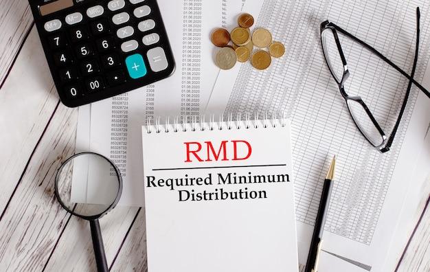 계산기, 현금, 안경, 돋보기 및 펜 근처의 흰색 메모장에 작성된 rmd