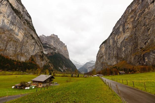有名なユングフラウへの玄関口、スイスアルプスのラウターブルンネンの村で美しい秋の時間。岩だらけの崖とro音が特徴の谷に設定