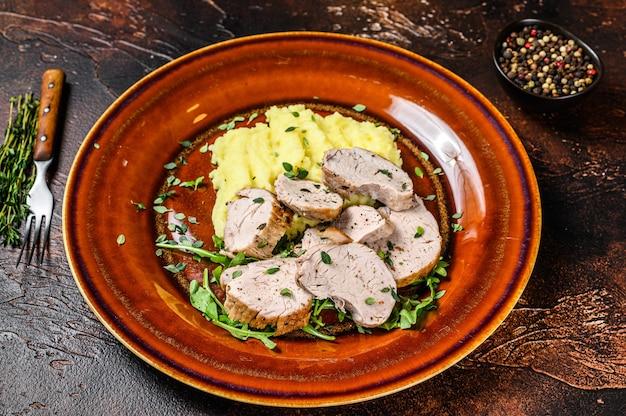 豚ヒレ肉のステーキをマッシュポテトと一緒にお皿に盛り付けました。暗い背景。