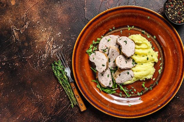 Roaast pork tenderloin meat steak on a plate with mash potato. dark background. top view. copy space.