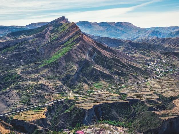 谷を渡る道。山の谷。遠くに伸びる岩だらけの棚。航空写真。