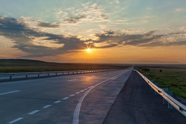 Впереди дорога и восход солнца, восход солнца на шоссе