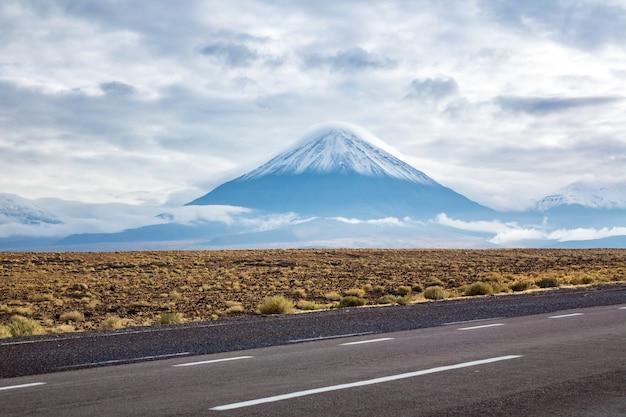Road in atacama desert savanna, mountains and volcano landscape, chile, south america