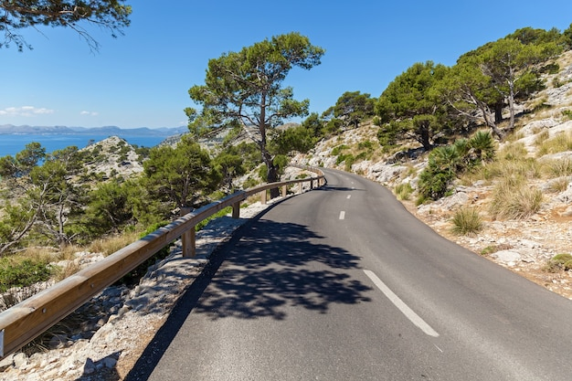 Road to the beach. asphalt road on the rocky coast of mallorca, that leads to the beach.