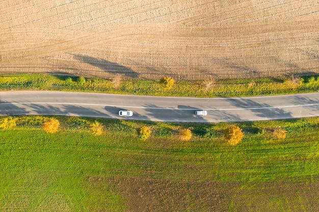Дорога между зеленым полем и обрабатываемой землей с желтыми деревьями на заходе солнца в осени с 2 автомобилями. вид с воздуха на асфальтовой дороге или аллее деревьев.