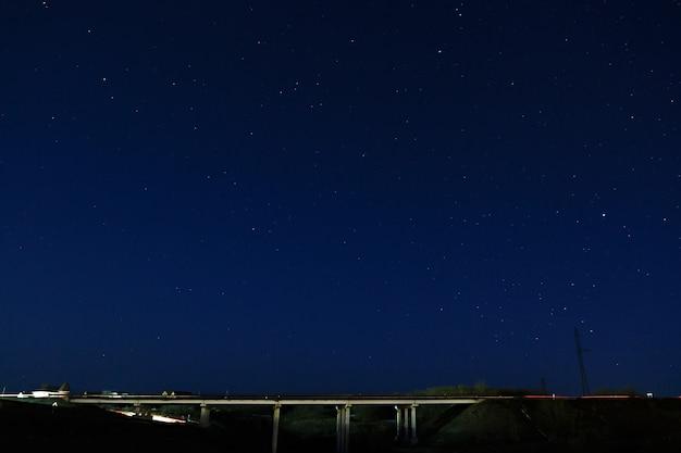 Автомобильный мост в ночном звездном небе.