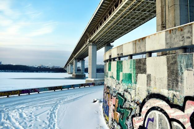 冬の凍った川に架かる道路橋