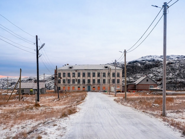 The road to the building of an old abandoned school against the backdrop of arctic hills in winter.