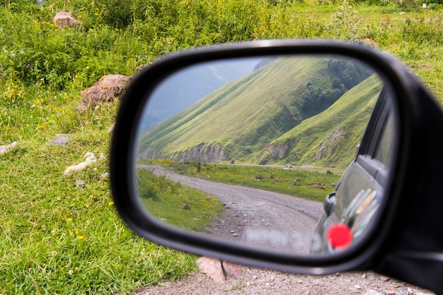 Road in the car mirror, side view