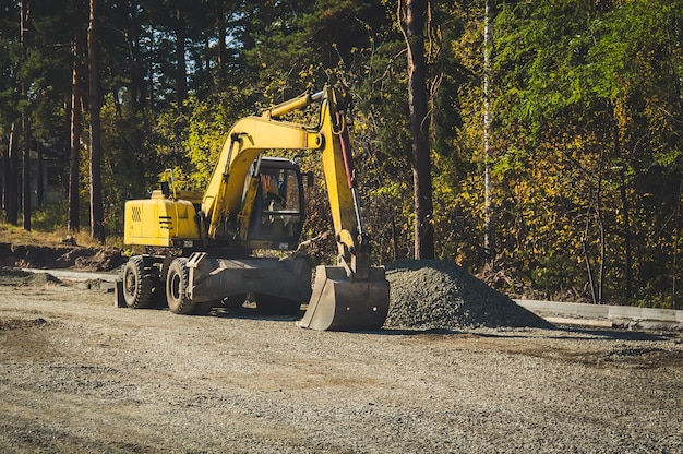 Road construction machines. road repair, asphalt laying. yellow wheeled excavator on the background of the forest.
