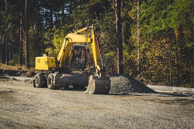 도로 건설 기계. 도로 수리, 아스팔트 깔기. 숲의 배경에 노란색 바퀴 굴착기.