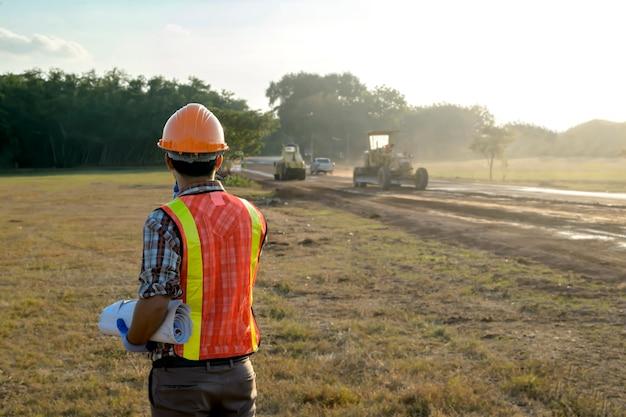 Руководитель дорожного строительства в настоящее время осматриваются работы и планирование дорожного строительства.