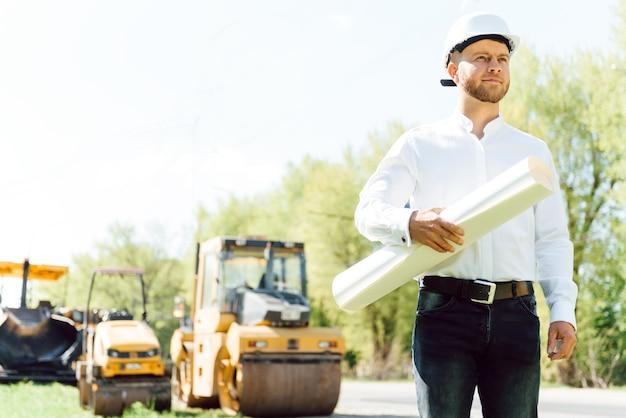 アスファルト舗装機械の近くの道路建設労働者。道路の修理。リンク近くのロードサービスワーカー。