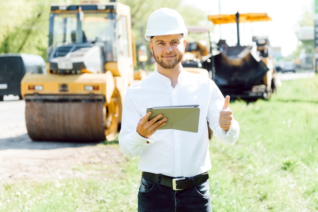 아스팔트 포장 재료 기계 근처 도로 건설 노동자. 도로 수리. 링크 근처 도로 서비스 노동자.