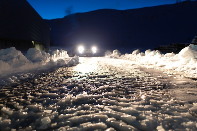 Road covered with ice in the headlights