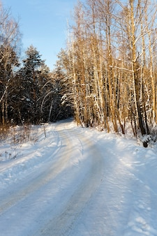 The road covered with snow during the winter.
