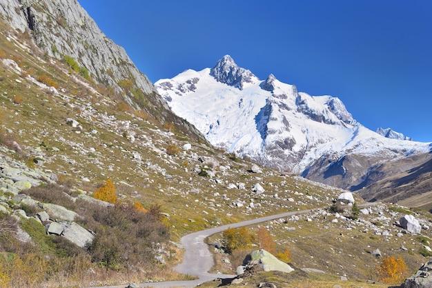 Euroean 알프스의 푸른 하늘 아래 눈 덮인 피크와 도로 횡단 산