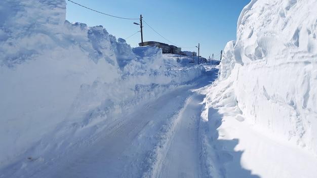 北極の雪に覆われた道路の側面に雪でいっぱいの道路