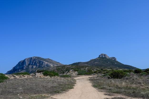 도로는 푸른 하늘 복사 공간에 대해 두 개의 높은 산을 향해 간다