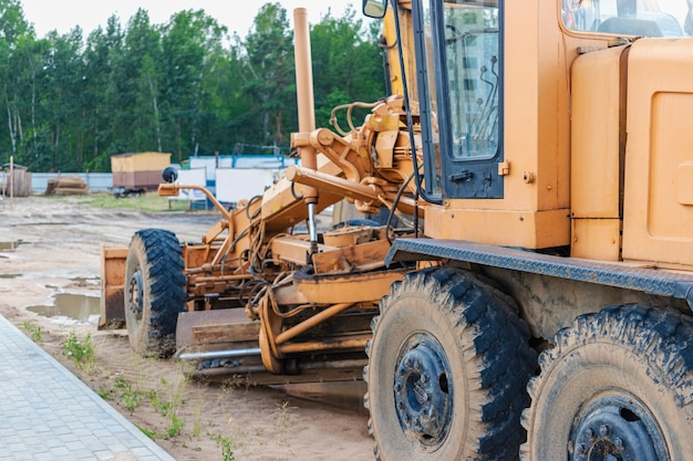 Road grader - heavy equipment for road construction and earthworks. leveling and improvement of the ground surface. construction of roads and transport communications.