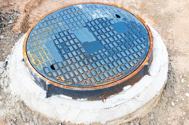 Дорожный люк для водоснабжения и канализации. крупный план. дорожные работы. доступ к подземным коммуникациям.