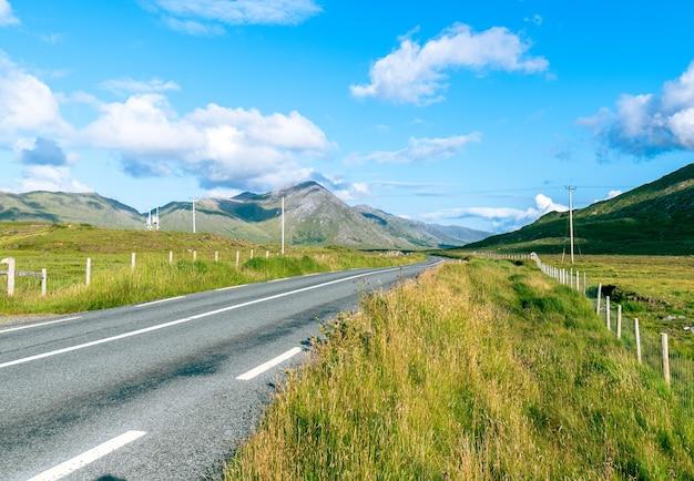 Дорога в коннемаре с видом на горы на горизонте. лето в ирландии.