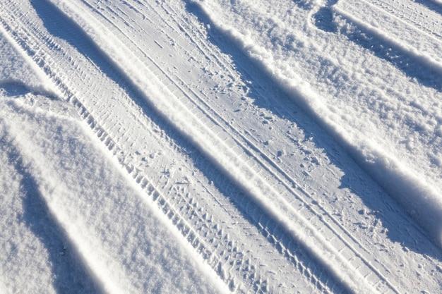 필드에 위치한 시골 도로. 연중 겨울철 도로에 눈이 내리고 표면에 자국이 보입니다. 클로즈업 사진