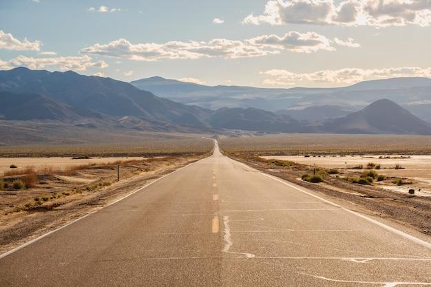 캘리포니아의 웅장한 산들이있는 사막 한가운데의 도로