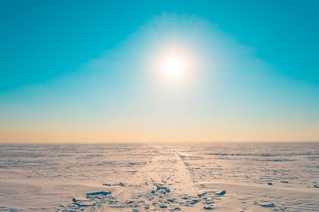 Дорога в снегу в зимней снежной пустыне, в бирюзовом небе светит яркое солнце.