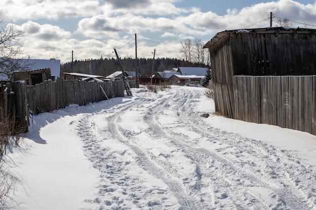 車のタイヤの痕跡で雪に覆われた村の道路。高品質の写真